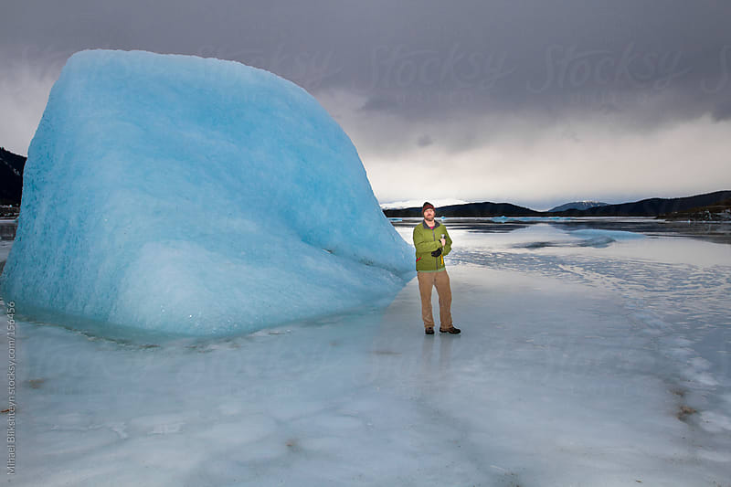 Man standing on a frozen lake by an iceberg by Mihael Blikshteyn for Stocksy United