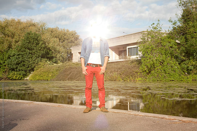Man reflecting light with a mirror in his face by Oscar Parasiego for Stocksy United