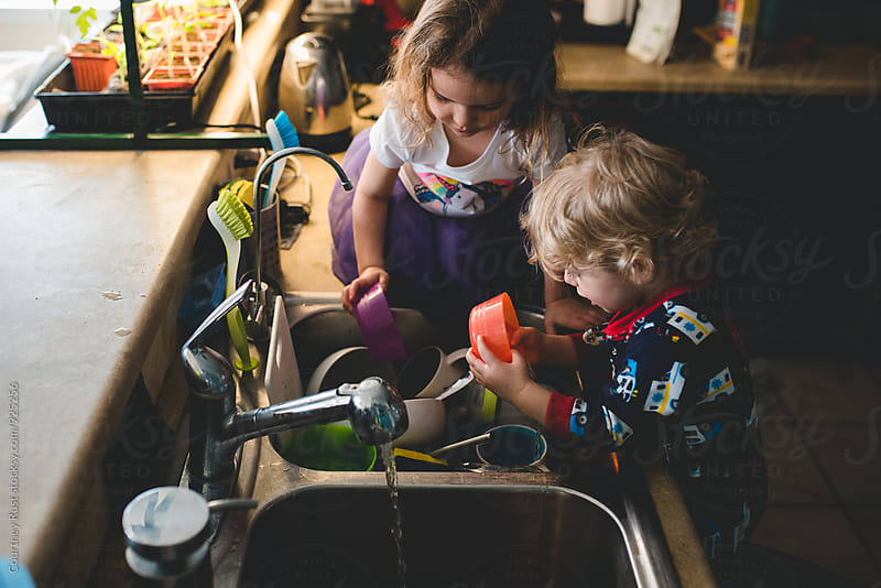 siblings washing dishes away by Courtney Rust for Stocksy United