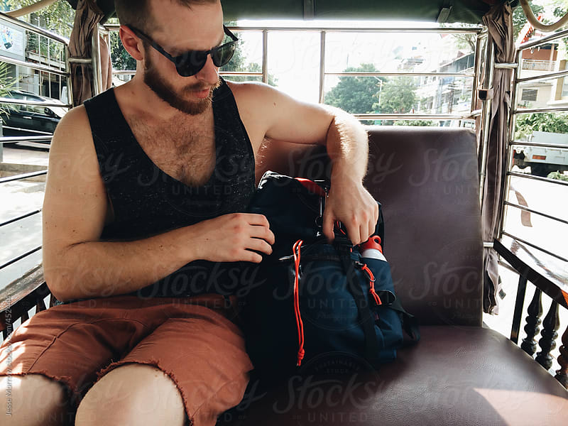 Young man gets in backpack while traveling  by Jesse Morrow for Stocksy United