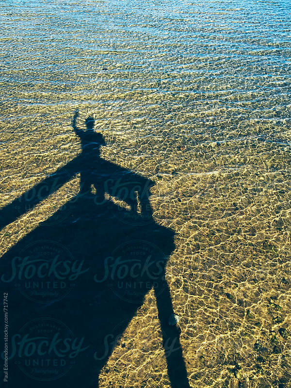 Shadow of man standing on dock above Lake Tahoe by Paul Edmondson for Stocksy United