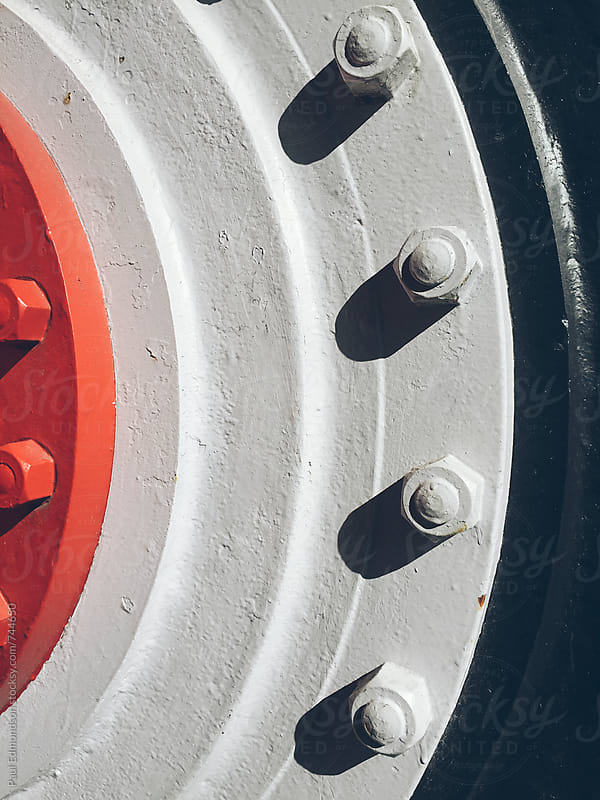 Bolts attached to large industrial wheel, close up by Paul Edmondson for Stocksy United