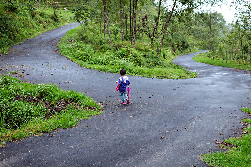 Little girl walking through a hilly road by Saptak Ganguly for Stocksy United