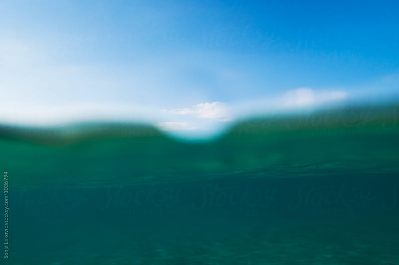 sea bottom and surface underwater and blue sky by Sonja Lekovic for Stocksy United
