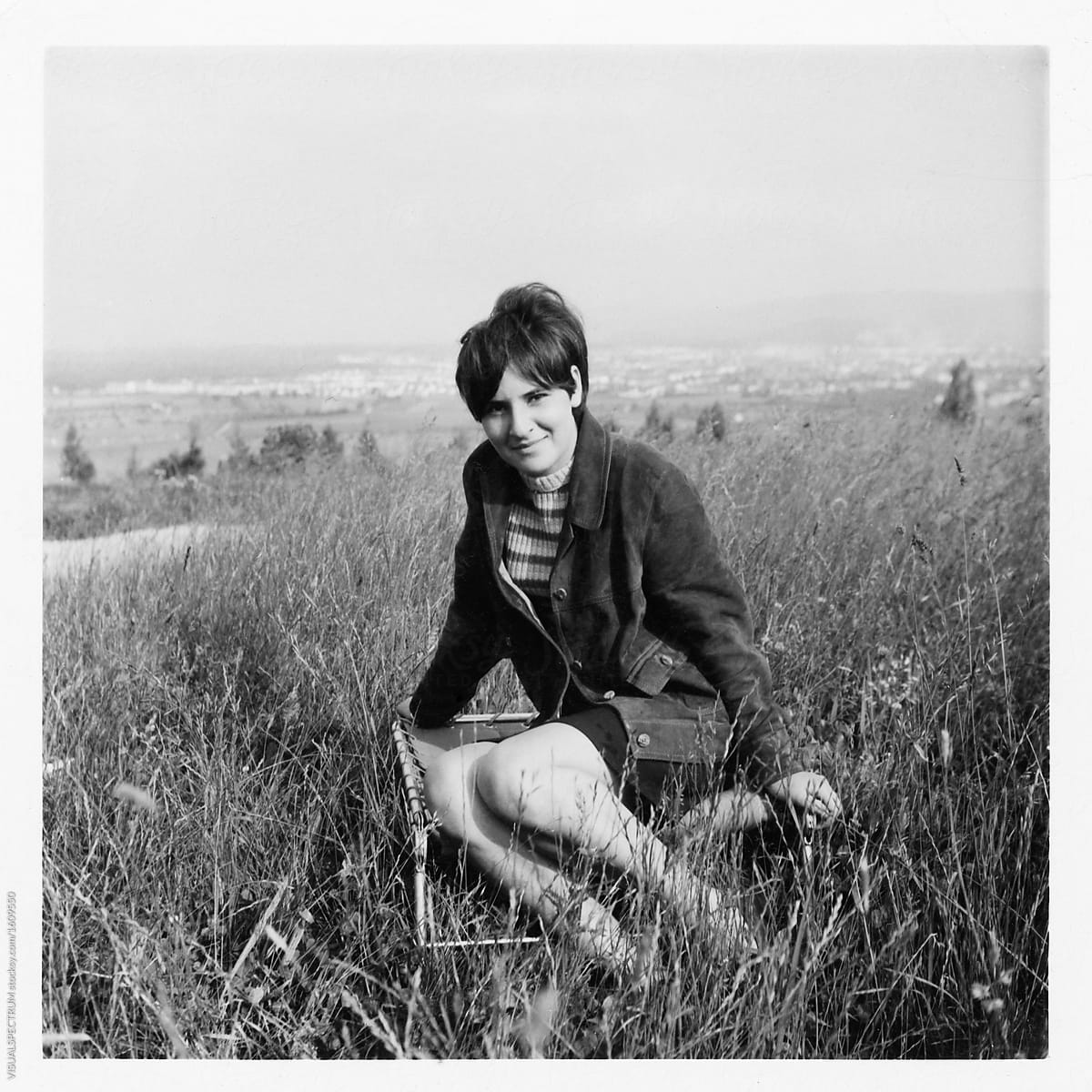 Scan of old 1960s black and white photograph of young woman sitt by visualspectrum for stocksy