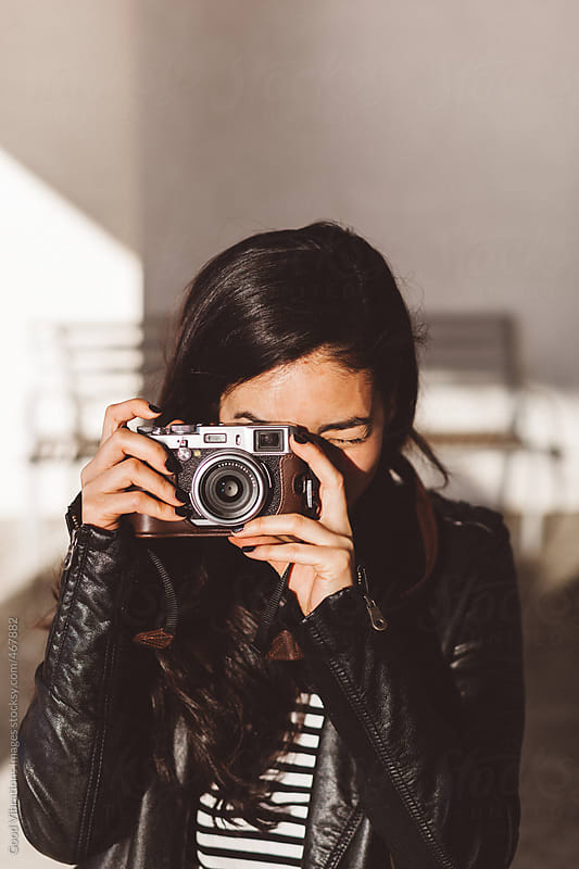Playful woman taking pictures with a digital camera by Good Vibrations Images for Stocksy United