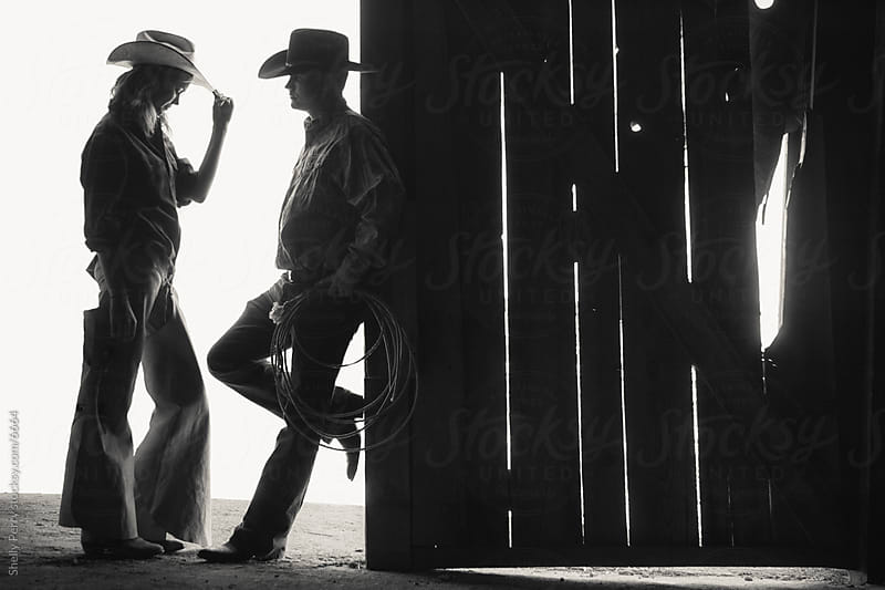Backlit Cowboy Couple Share an Intimate Moment in Silhouette by Shelly Perry for Stocksy United
