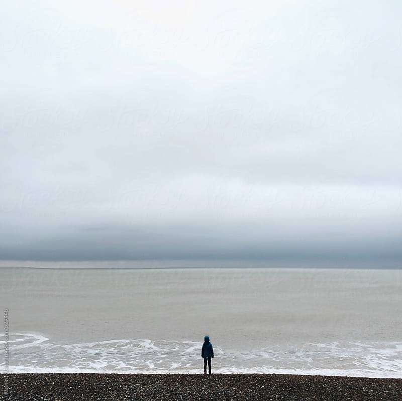 Boy looking at the sea. by Kirstin Mckee for Stocksy United