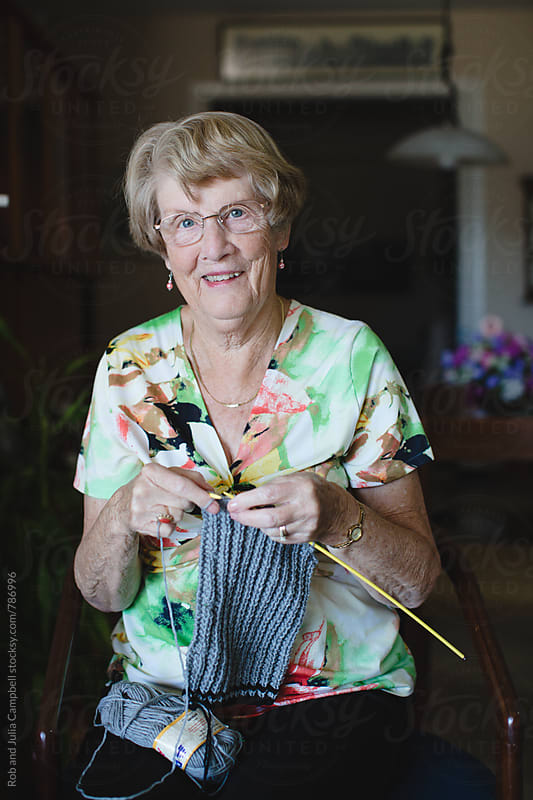 Happy portrait of senior woman knitting inside by Rob and Julia Campbell for Stocksy United