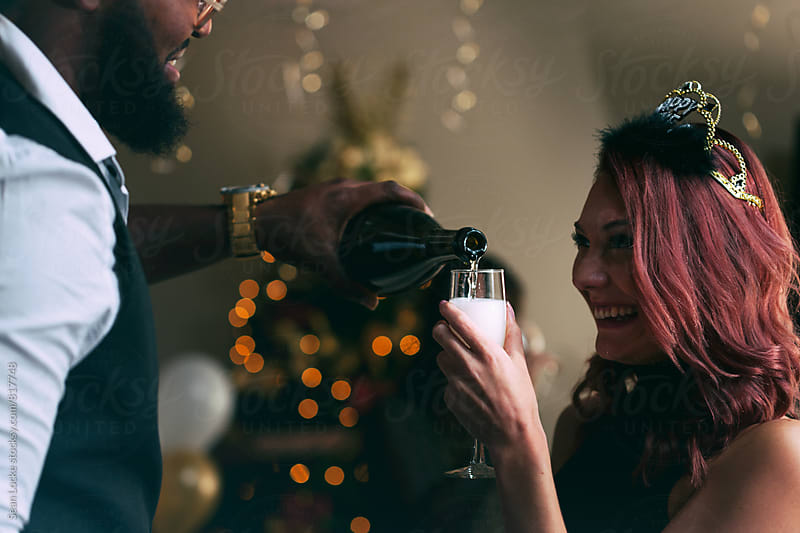 NYE: Man Pours Champagne Into Glass For Friend by Sean Locke for Stocksy United