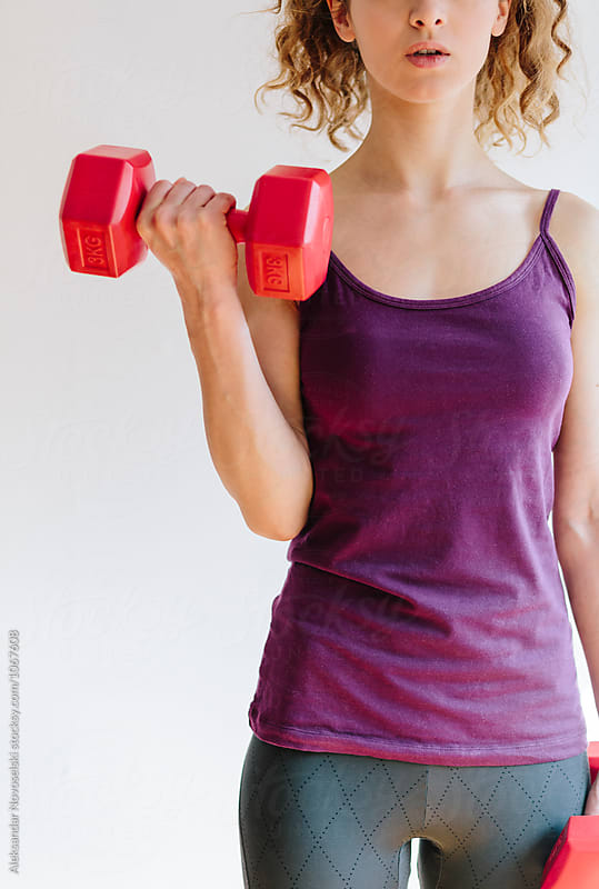 Young woman making excercises with dumbbells by Aleksandar Novoselski for Stocksy United