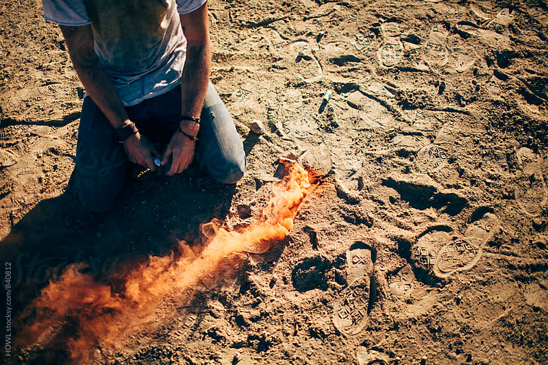 A man kneeling in the dirt next to a trail of fire by HOWL for Stocksy United