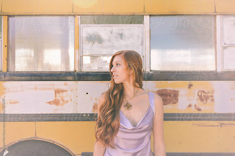 A Redheaded Woman in Lavender with a School Bus by Briana Morrison for Stocksy United