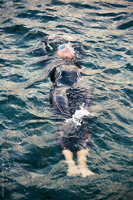 Woman wearing a wetsuit floating in water. by BONNINSTUDIO for Stocksy United