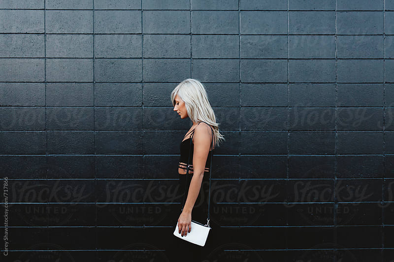 Profile of stylish woman looking down against black wall by Carey Shaw for Stocksy United