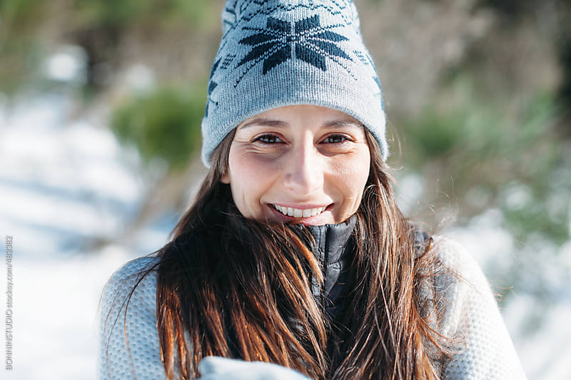Portrait of a happy young woman on a cold snowy day. by BONNINSTUDIO for Stocksy United