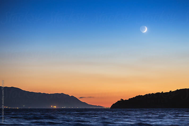 Crescent Moon over a Seascape at Twilight by Helen Sotiriadis for Stocksy United