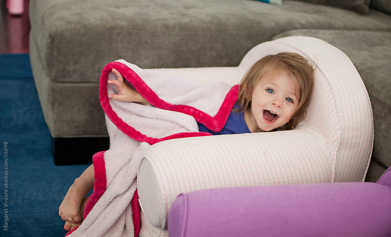 little girl playing peek-a-boo by Margaret Vincent for Stocksy United