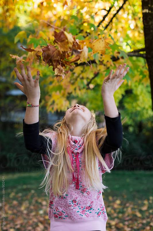 Young girl plying at the park in autumn by Mauro Grigollo for Stocksy United