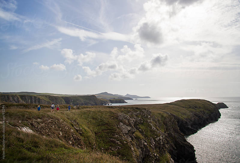 A view across a rugged coastline by Helen Rushbrook for Stocksy United