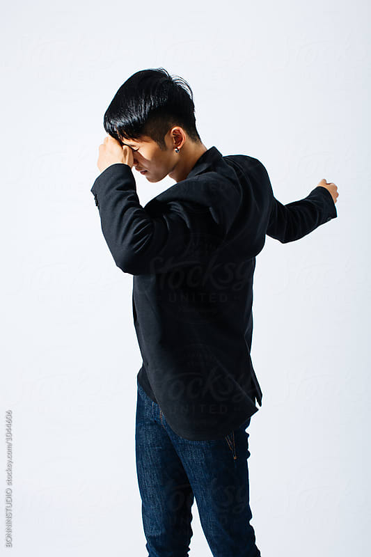Portrait of a stylish asian man covering his face over white background. by BONNINSTUDIO for Stocksy United