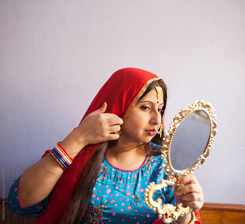 Young Indian woman with traditional dress and ornaments and looking at the mirror  by PARTHA PAL for Stocksy United