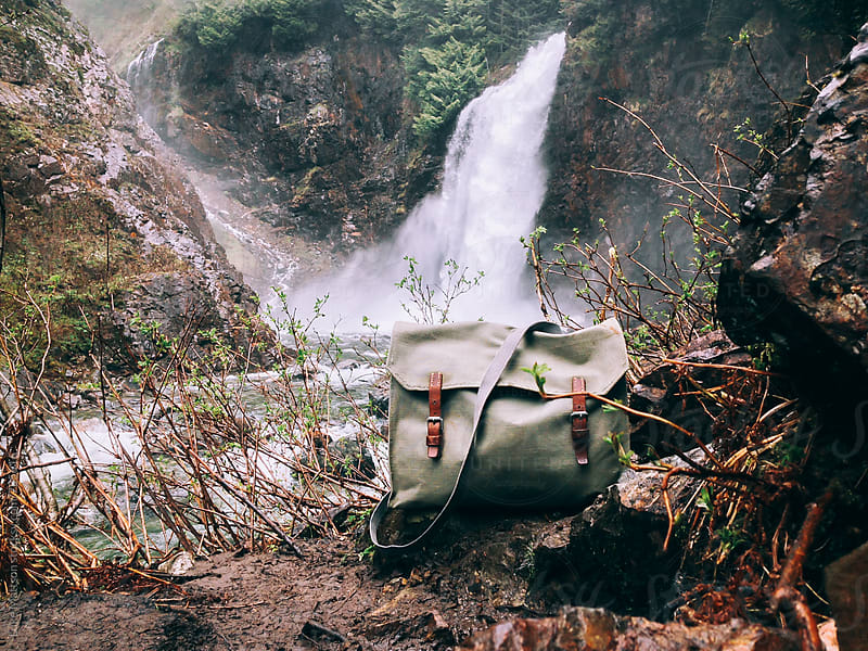 Old Swiss Army Bag With Leather Buckles On Ground In Front Of Flowing Waterfall by Luke Mattson for Stocksy United