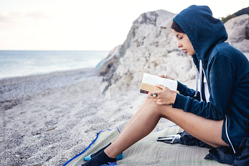 Young Woman Reading a Book on the Beach by Helen Sotiriadis for Stocksy United