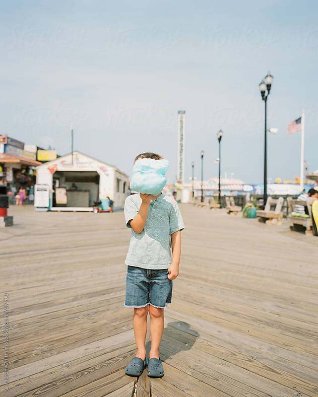 Young boy hiding behind his cotton candy on a Jersey Shore boardwalk by Cameron Whitman for Stocksy United