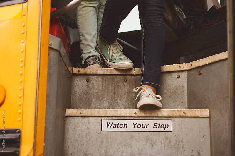 Students  walk down the steps of a school bus by Tana Teel for Stocksy United