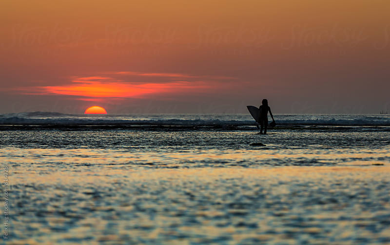 Surfer in front of the setting sun by Felix Hug for Stocksy United
