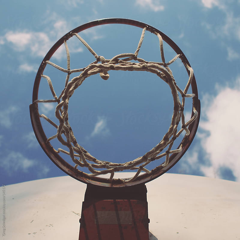 Basketball hoop, rim, net and backboard under a clear blue sky by Greg Schmigel for Stocksy United