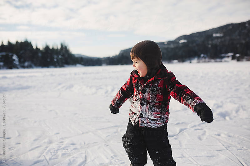 Happy little boy running in the snow by Rob and Julia Campbell for Stocksy United