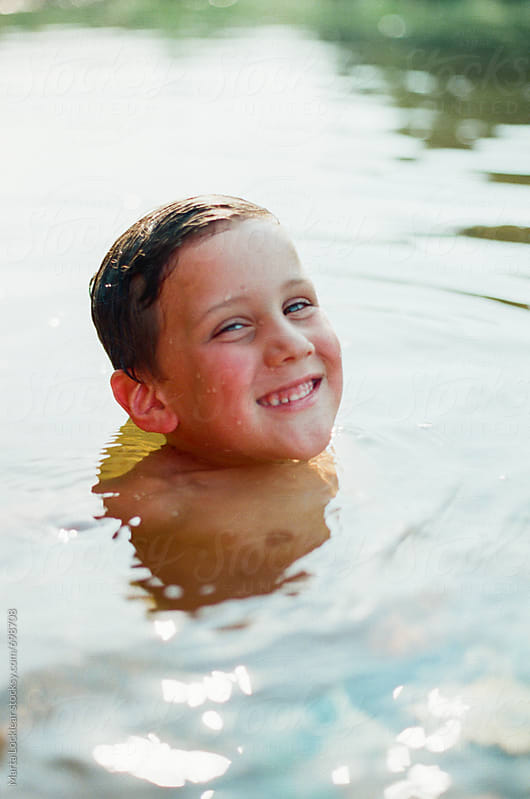 Boy smiling and popping his head out of the water by Marta Locklear for Stocksy United