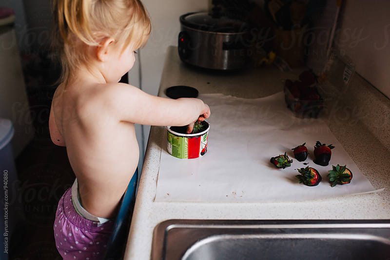 Cute toddler girl with pigtails making chocolate covered strawberries. by Jessica Byrum for Stocksy United