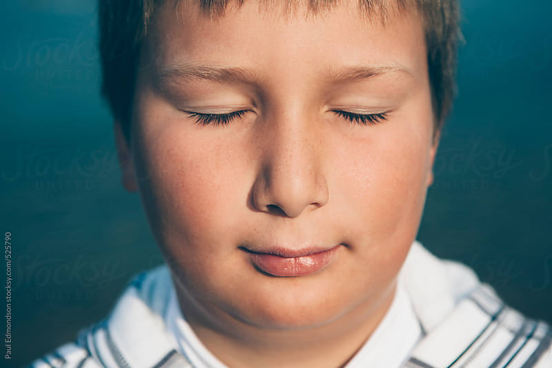Portrait of ten year old boy with eyes closed, close up by Paul Edmondson for Stocksy United