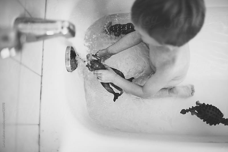 A little boy playing with dinosaurs in the bath tub. by Sarah Lalone for Stocksy United