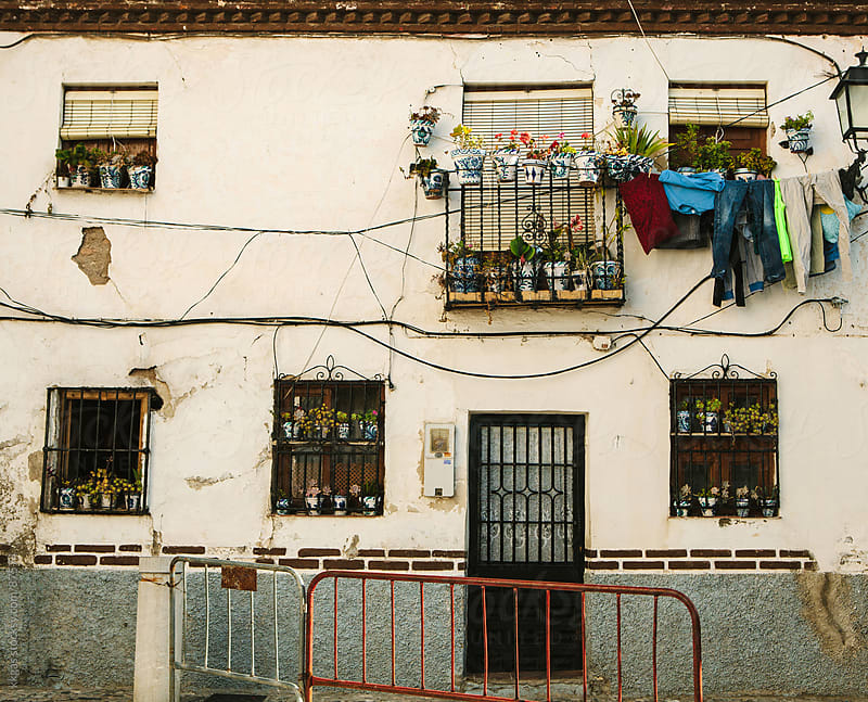 Facade of a house with plant pots and washing hanging from the window. by kkgas for Stocksy United