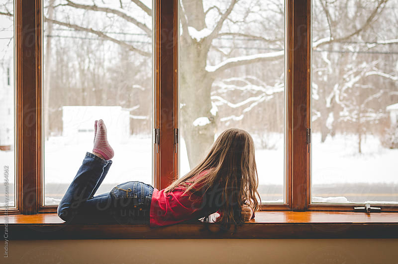 Girl lying beside a snowy window by Lindsay Crandall for Stocksy United