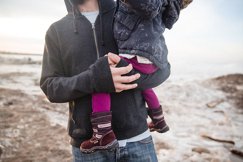 father holds daughter at the beach in the winter by Maria Manco for Stocksy United