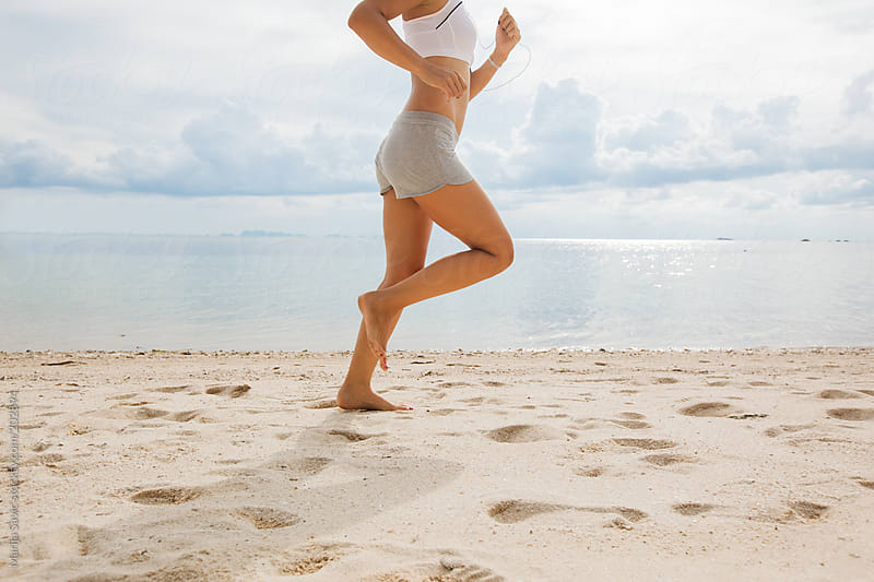 Fit Woman Jogging on the Beach by Marija Savic for Stocksy United