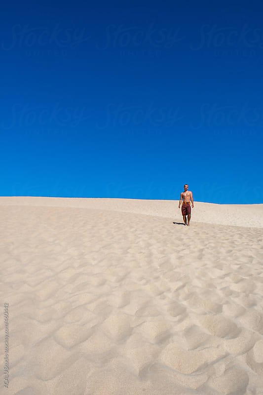 Man waiting on dune in Cadiz beach by ACALU Studio for Stocksy United