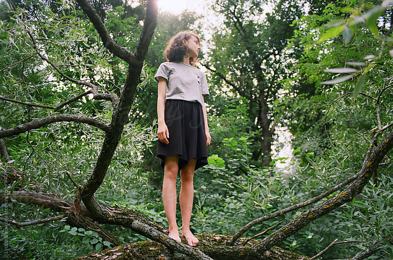 Young woman standing on a tree by Liubov Burakova for Stocksy United