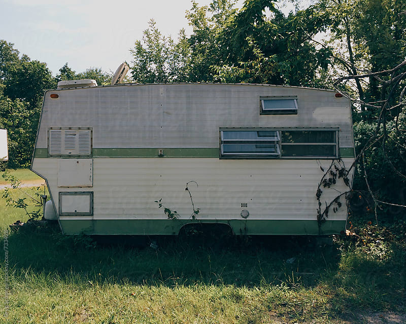 An abandoned mobile home travel trailer camper home in a forest, trailer park by Greg Schmigel for Stocksy United