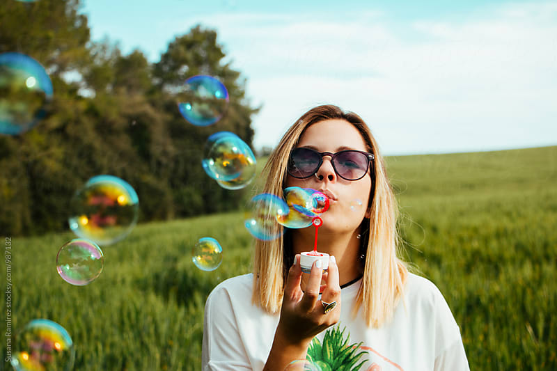 Portrait of young woman blowing bubbles by Susana Ramírez for Stocksy United