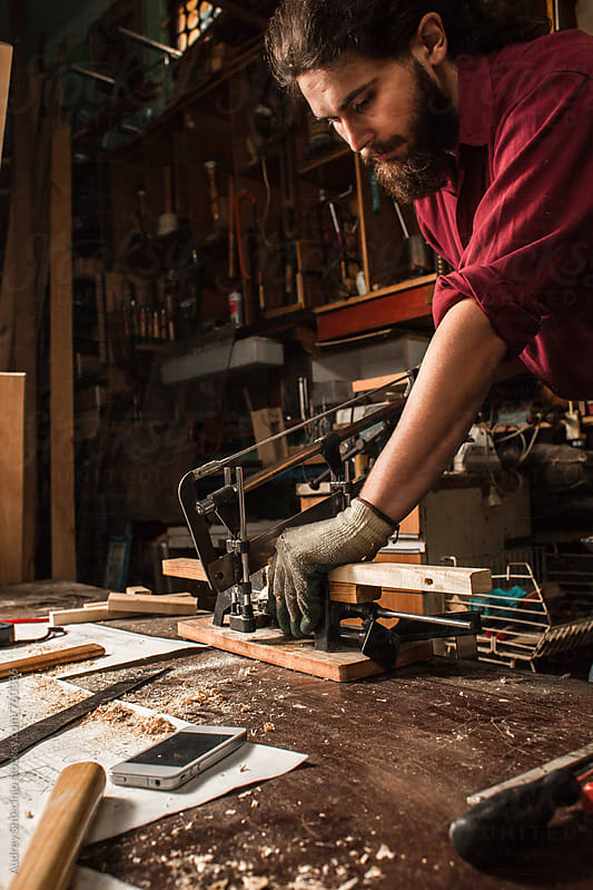 Carpenter working in his rustic workshop. by Audrey Shtecinjo for Stocksy United