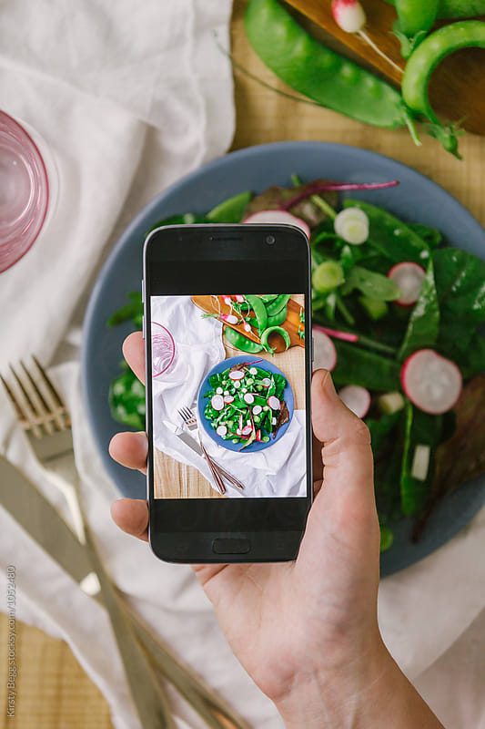 Woman takes a photo on her smartphone of her salad by Kirsty Begg for Stocksy United