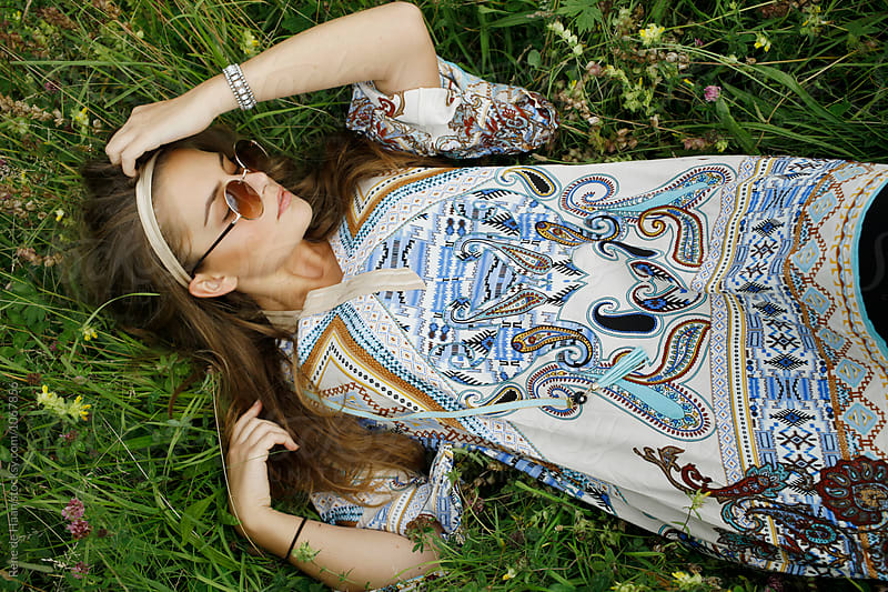 young bohemian-style woman lying in grass by Rene de Haan for Stocksy United