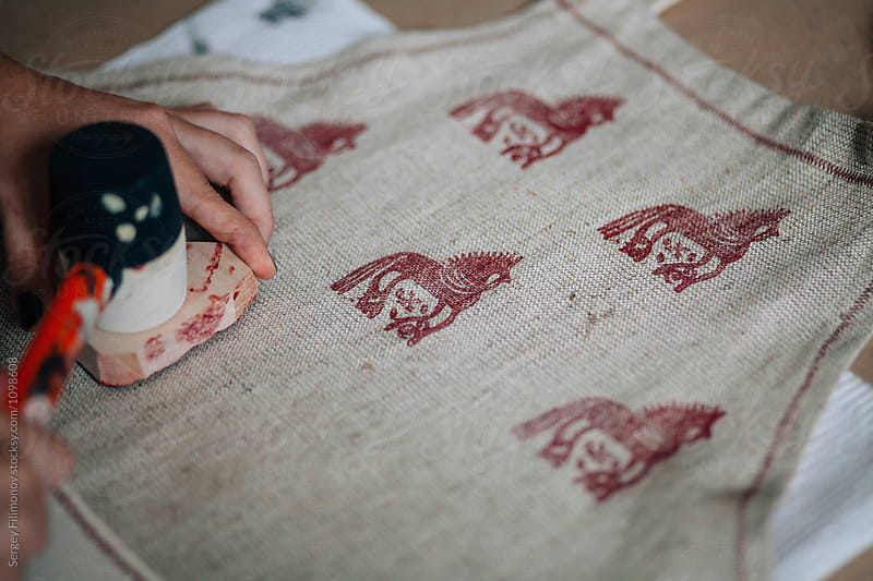 Girl is engaged in stamping on fabric by Sergey Filimonov for Stocksy United