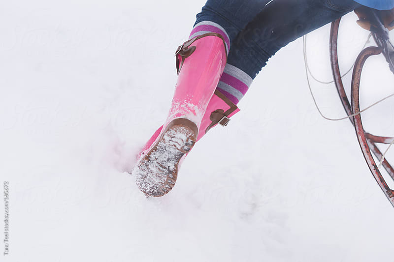 A girl runs through the snow with a sled by Tana Teel for Stocksy United